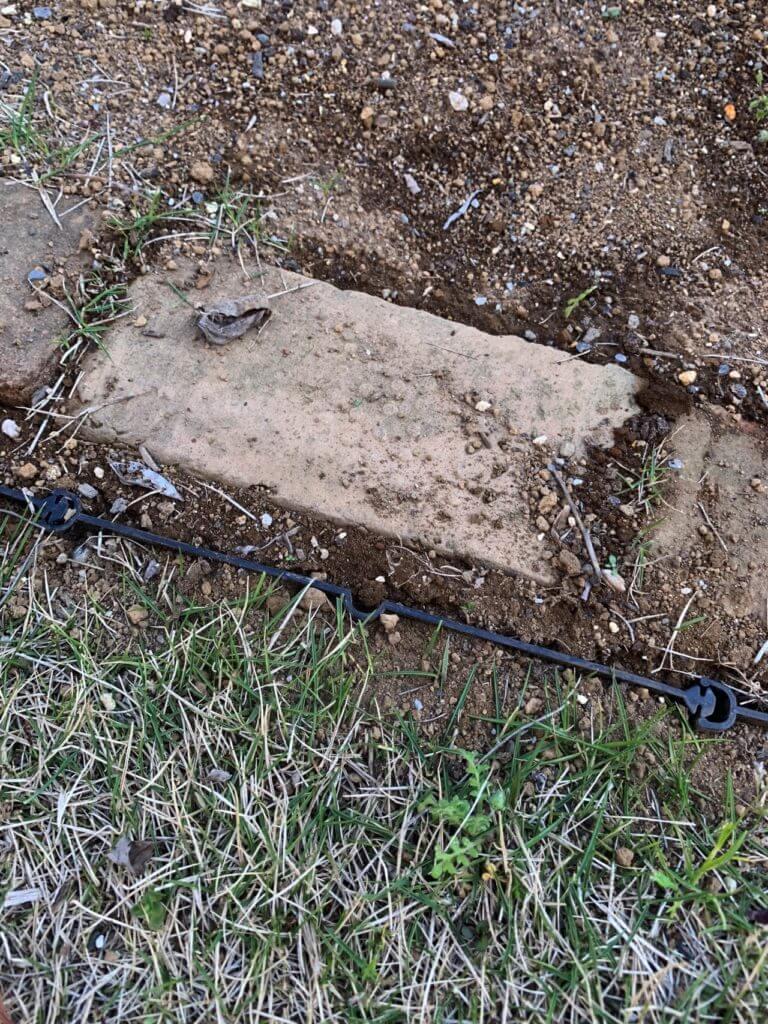 芝の侵入を防ぐために地面に埋め込まれた根止めの板仕切り
